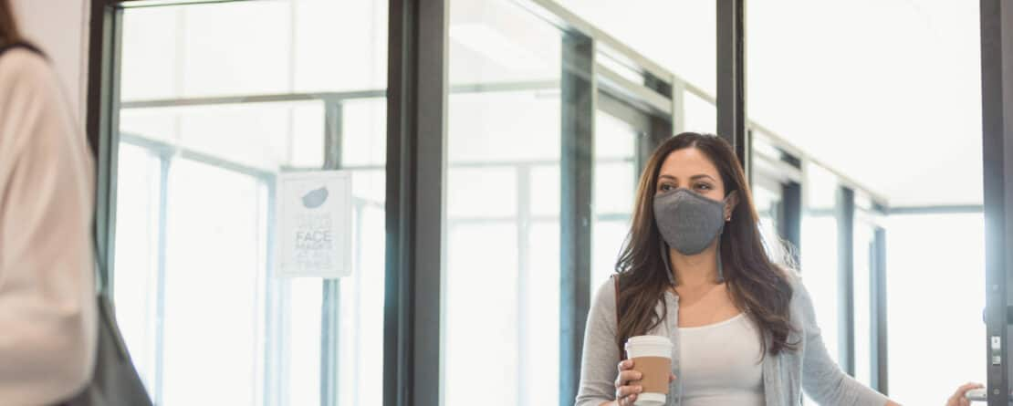 woman wearing protective mask while entering office building